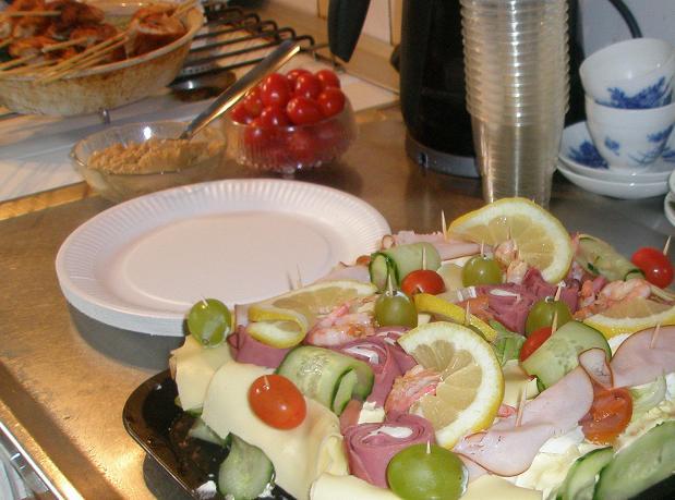 Det är dukat till studentmottagning, med smörgåstårta, kycklingspett och tillbehör.